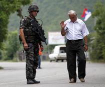 Un sarb din nordul Kosovo trece pe langa un soldat Kfor (NATO)