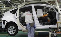 Un muncitor lucreaza pe linia de asamblare pentru Toyota Prius