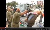 Un ofiter israelian loveste cu pusca un militant pro-palestinian