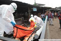 Monrovia, Liberia: Angajati din Sanatate ridica intr-o masina corpul unei persoane infectate cu Ebola