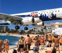 Un avion aterizeaza deasupra turistilor