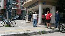 Grecii stau la coada pentru a scoate bani din bancomate