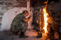 Soldat ucrainean pregatind lampa cu gaz