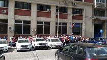 Mai multe persoane asteapta in fata sediului Politiei Romane din Capitala