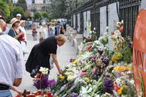 O femeie depune flori in fata Palatului Regal
