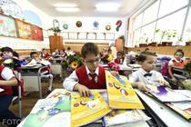 Elevi rasfoind manuale scolare in clasa
