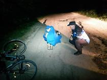 Biciclist ranit, ajutat de un caine