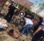 Politist lovește barbati intins pe jos, in Bolintin