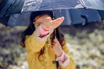 Copil jucandu-se in ploaie