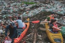 Voluntari care curăță un lac de gunoaie