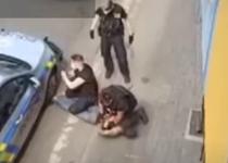 tanar rom la pamant in timp ce un politist ii preseaza gatul