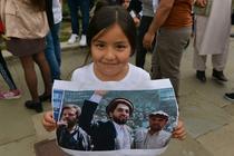 Copil tinand o imagine cu Ahmad Massoud (centru)